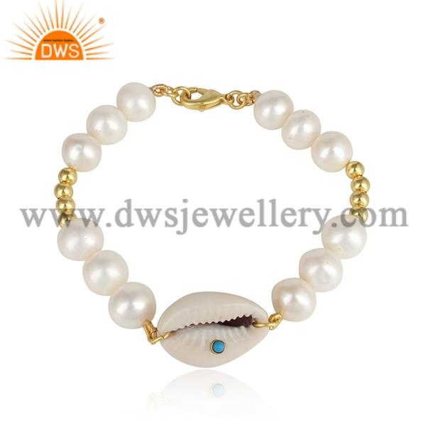 Cowrie centered, pearl and turquoise brass gold bracelet
