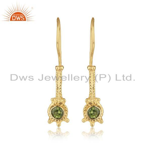 Designer long earring in yellow gold on silver with shiny peridot