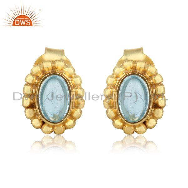 Designer handmade stud in yellow gold on silver with blue topaz