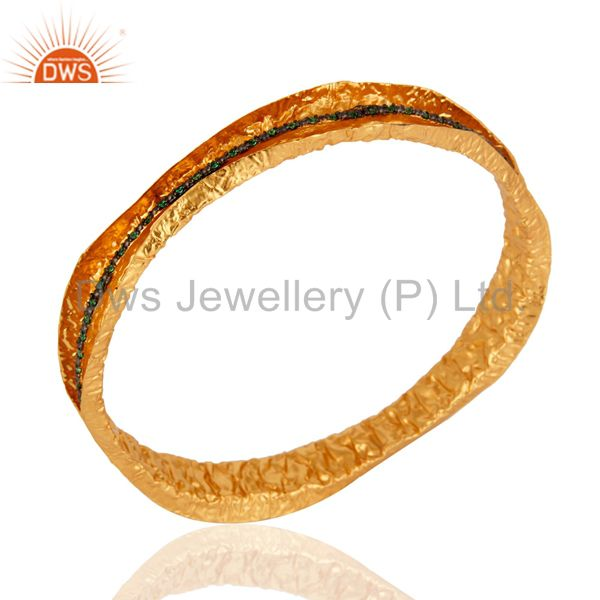 Supplier of 24k yellow gold on artisan made designer bangle green cubic zirconia