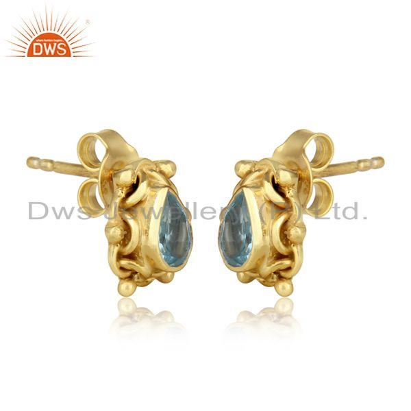 Handmade dangle earring in yellow gold on silver with blue topaz