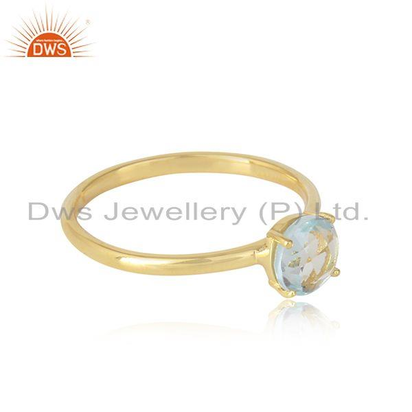 Solitaire ring in yellow gold on silver with natural blue topaz