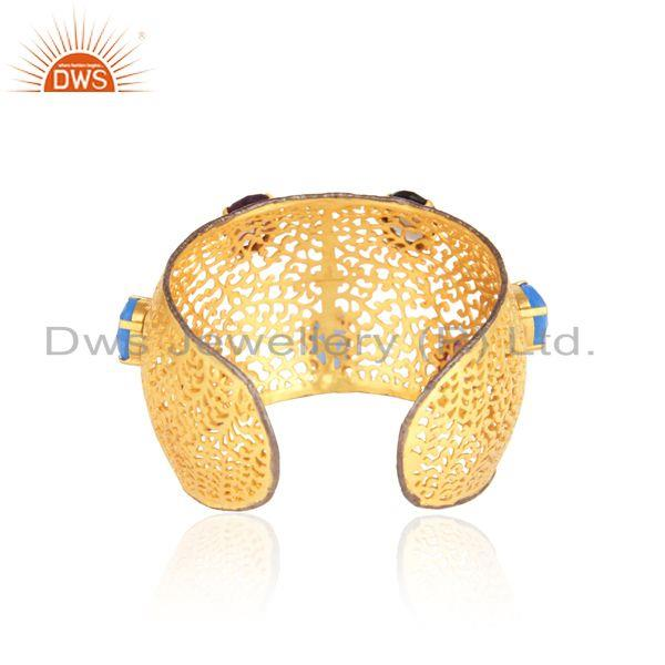 Designer of Bold filigree cuff in yellow gold on silver with multi gemstones
